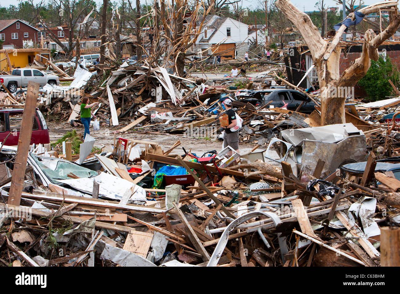 Survivors walk through a field of debris in Joplin, Missouri, May 25, 2011. - Stock Image