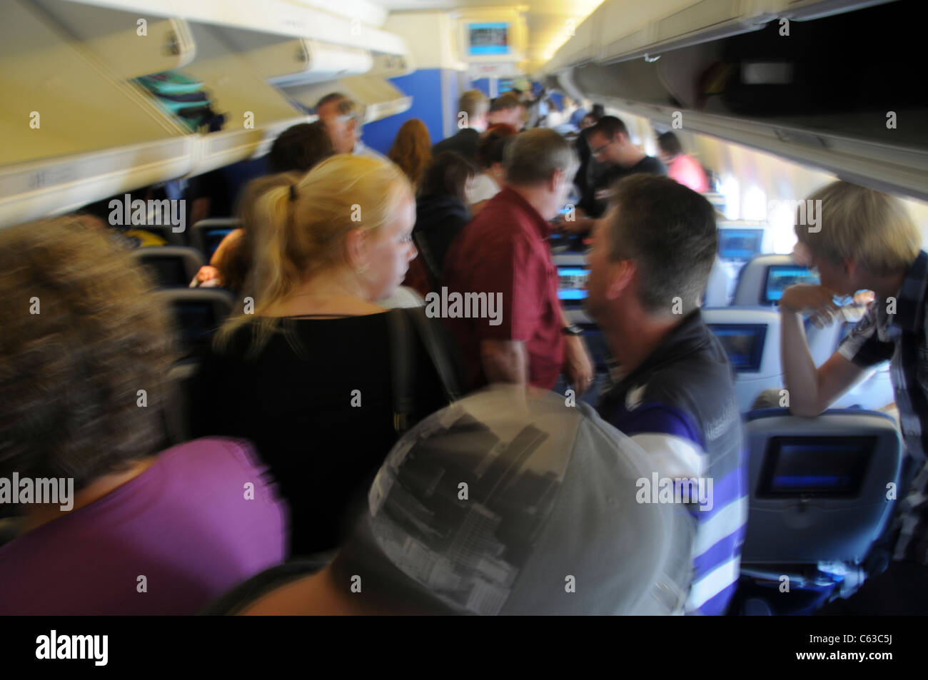 Air passengers placing or removing carry on luggage from overhead compartments - Stock Image