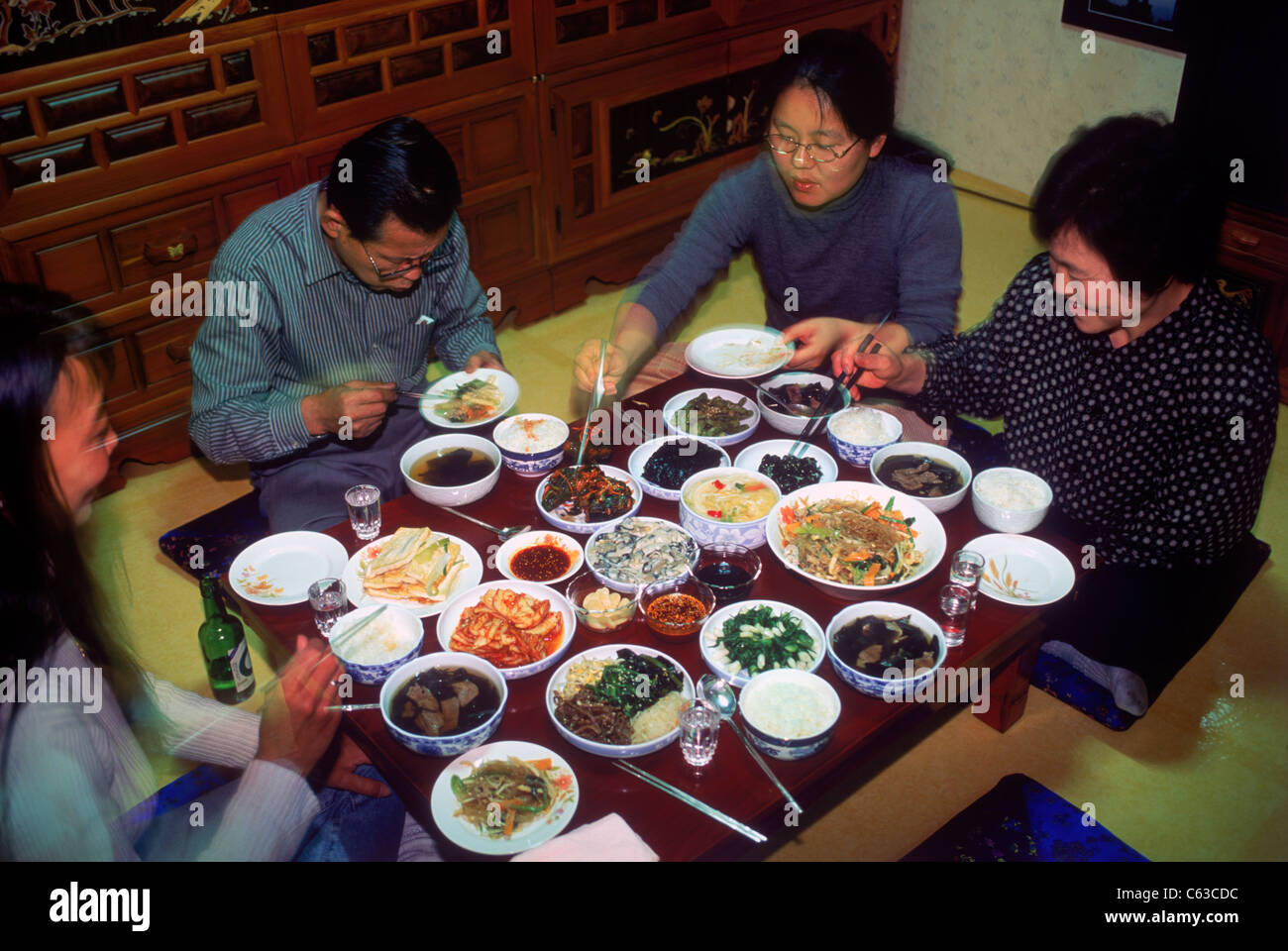 Family sitting at dinner table eating variety of home made Korean foods in South Korea - Stock Image
