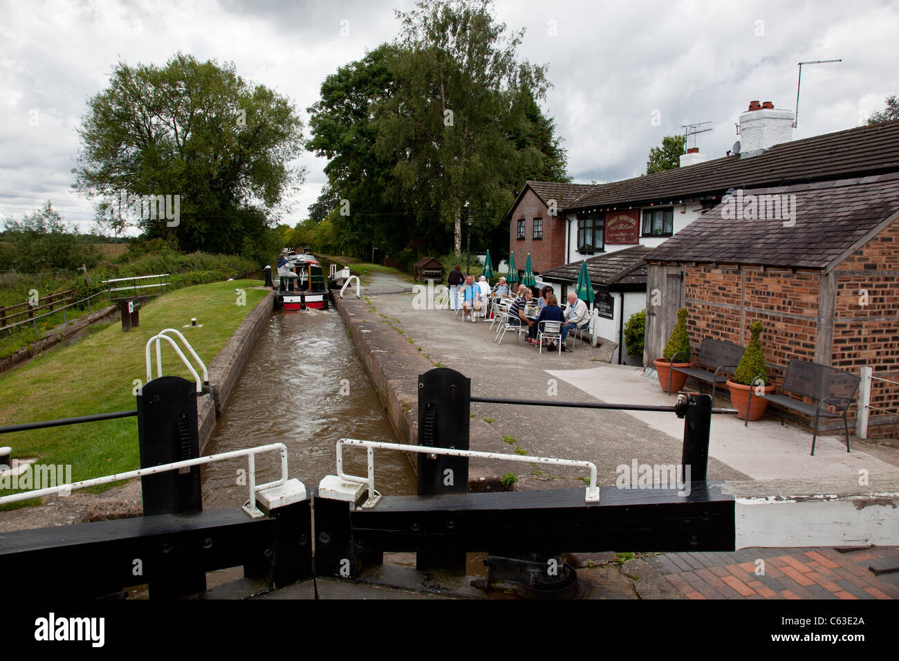 Canal boat leaving the lock at Willey Moor, on the Llangollen Canal near Whitchurch, Shropshire - Stock Image