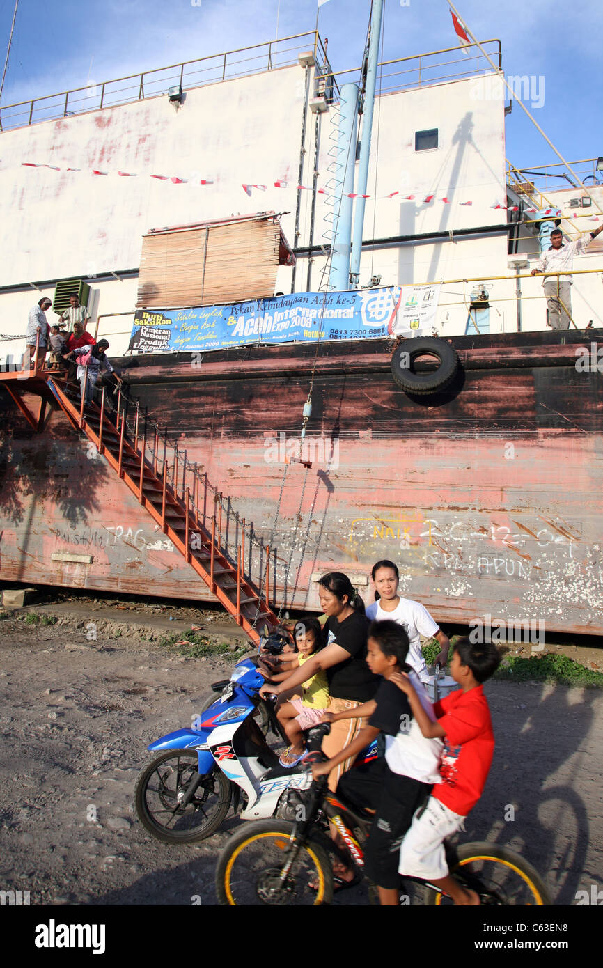 People riding past ship which was moved four kilometers inland during the boxing day tsunami of 2004. Banda Aceh, - Stock Image