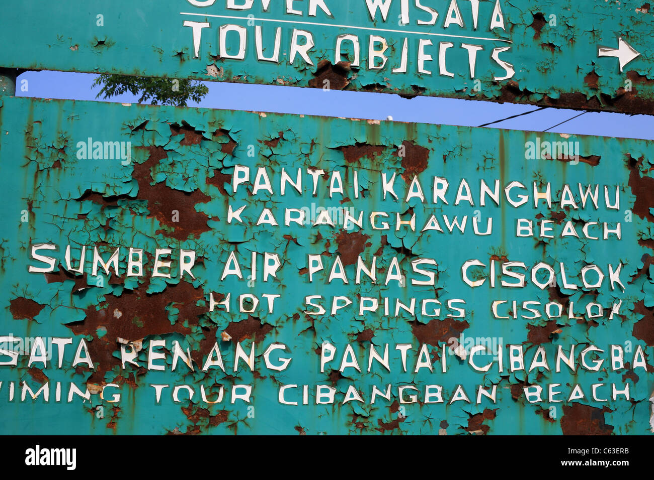 Rusty and flaking tourist sign showing local attractions in English and Indonesian, Pelabuhanratu, West Java, Java, - Stock Image