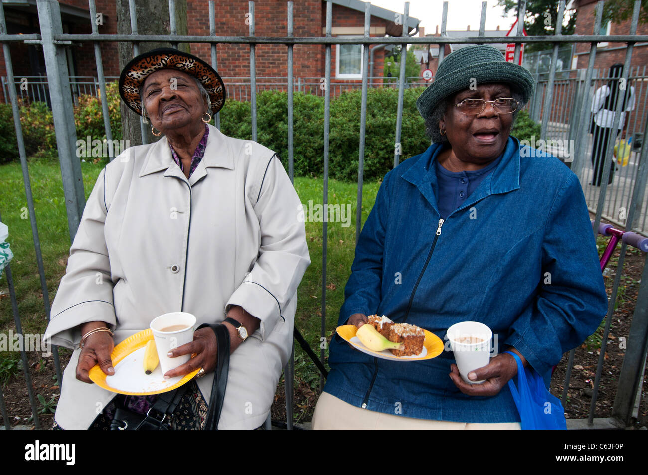 Clarence Road Hackney. Street tea party one week after the riots.Two elderly Afro Caribbean women with tea and cake - Stock Image