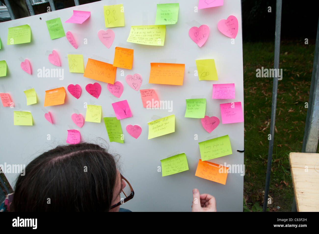 Clarence Road Hackney. Street tea party one week after the riots.Woman looking at post-it note messages on message - Stock Image