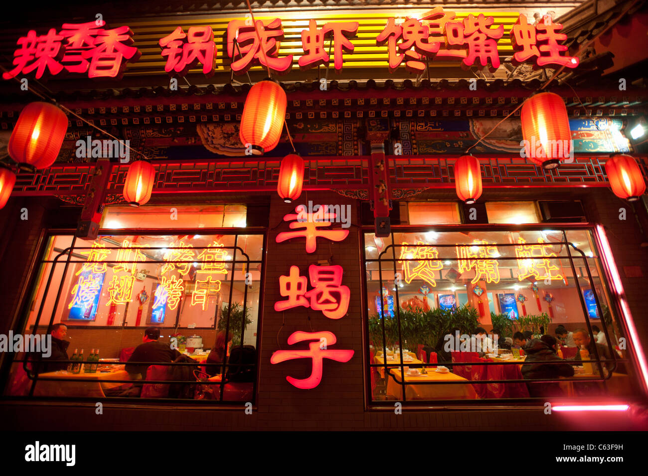 Neon signs and red lanterns at night  illuminating menu at Chinese restaurant in Beijing China - Stock Image