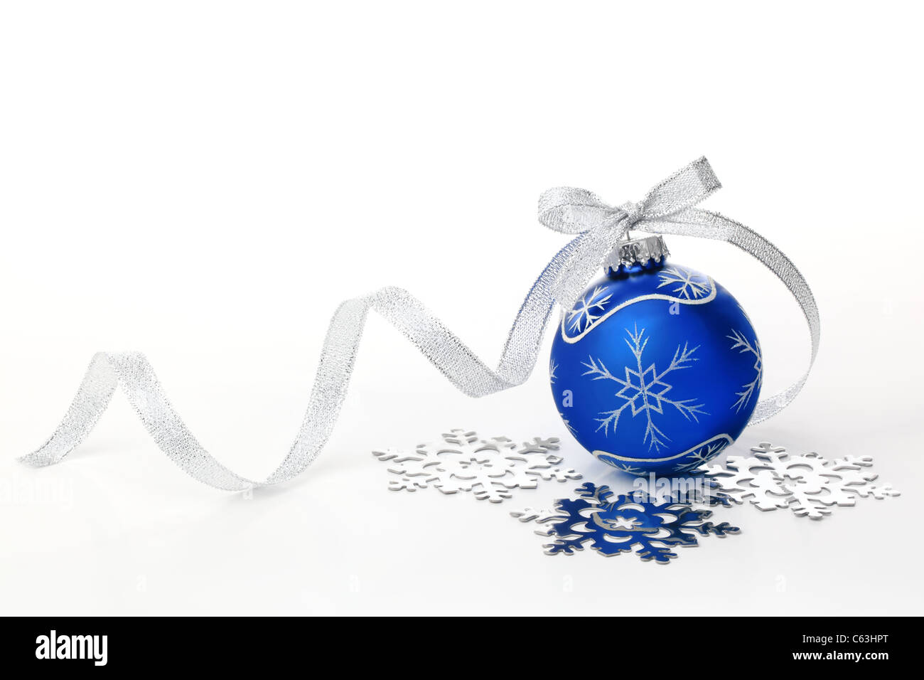 Blue christmas ball with silver ribbon bow and snowflake on white background. - Stock Image
