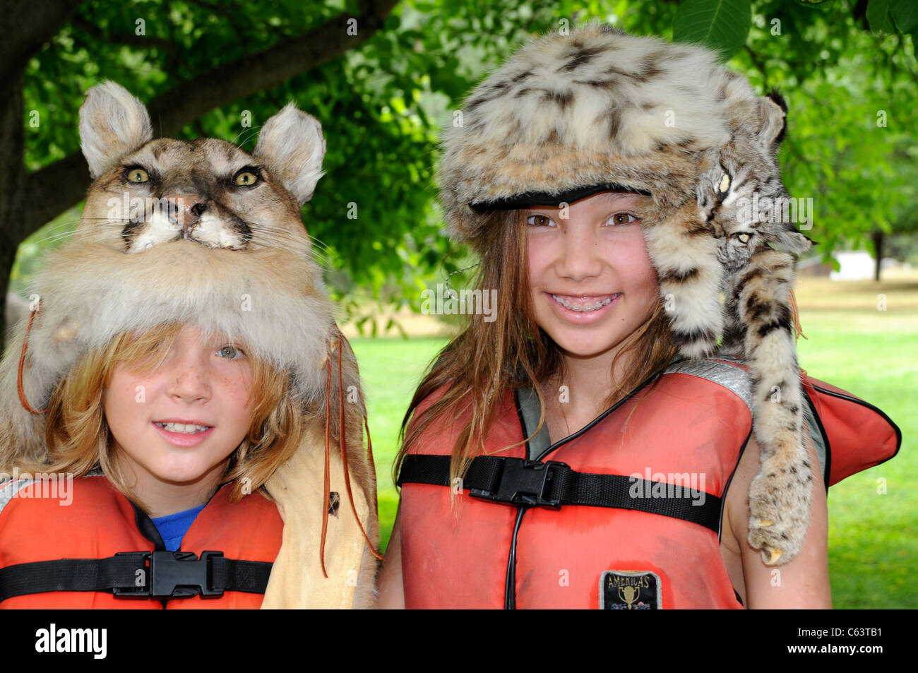 Boy and girl 8-12 years wearing wild cat fur hats during Salmon River rafting trip in Idaho - Stock Image