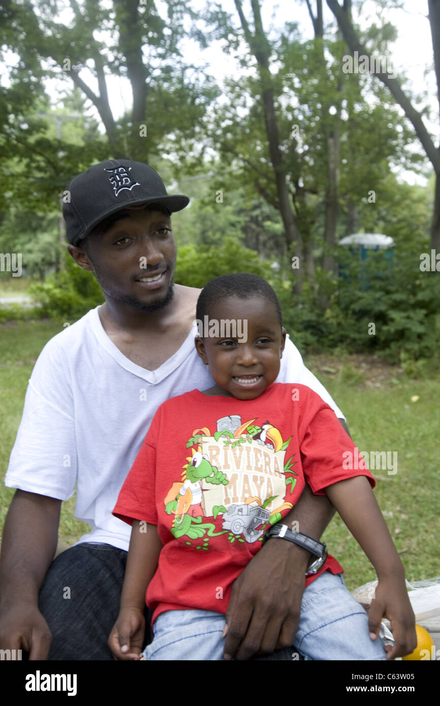 Portrait of a young man with child who works with a childcare center in inner city Detroit. - Stock Image