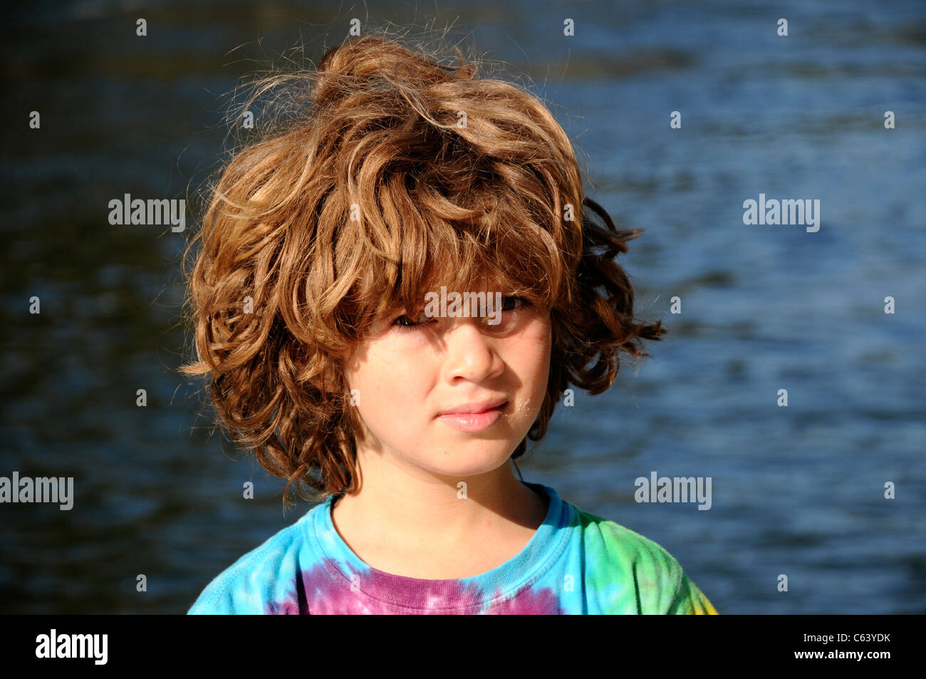 Young boy waking up on Salmon River rafting trip with wild scraggly auburn red hair - Stock Image