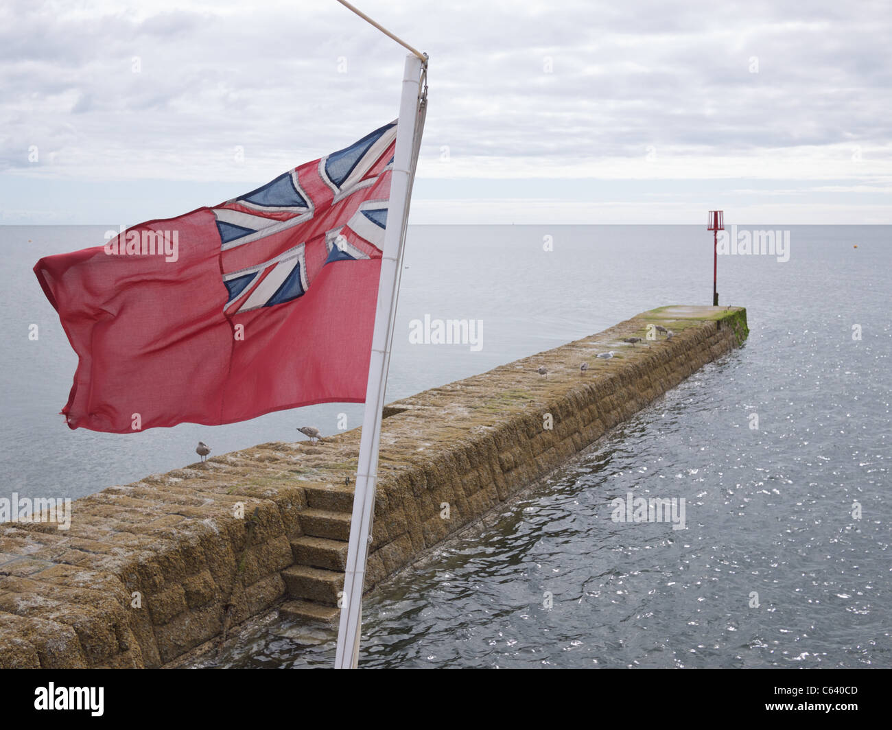 Red Duster Flag on the back of a boat, Dawlish, Devon. - Stock Image