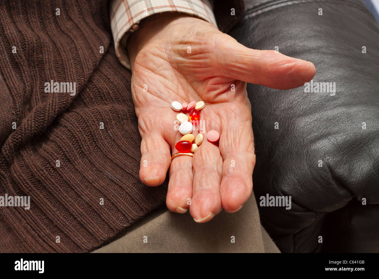 An elderly man holds out his hand with an assortment of pills - Stock Image