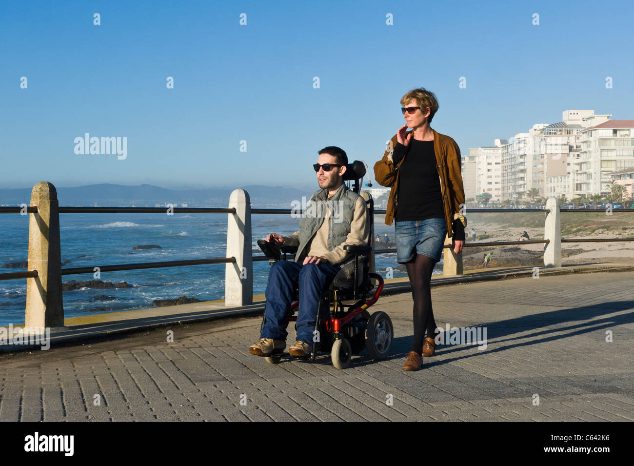 Person in a wheelchair with carer enjoying an outing at Beach Road in Cape Town South Africa - Stock Image