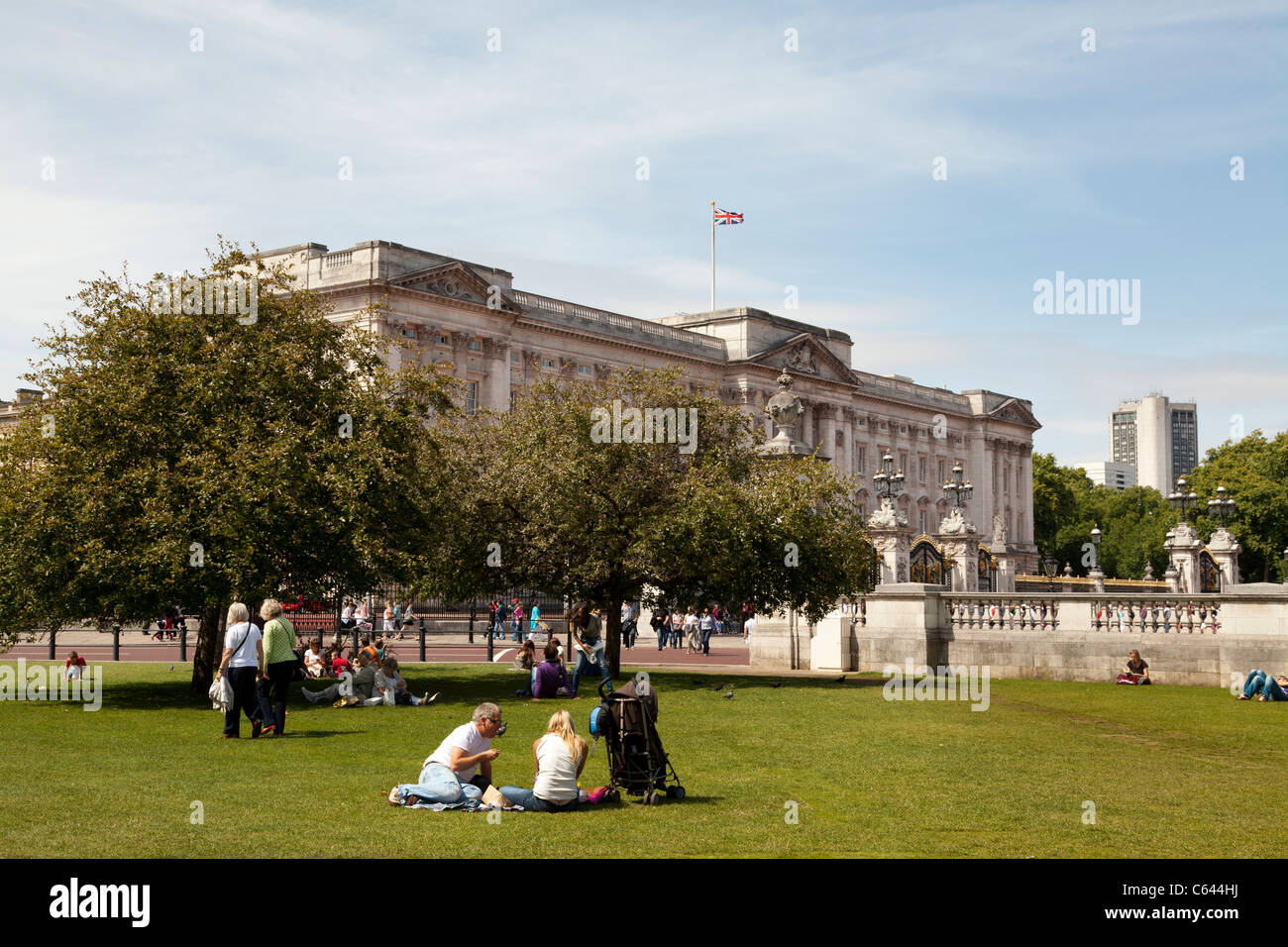 Tourists resting on the grass outside Buckingham Palace - Stock Image