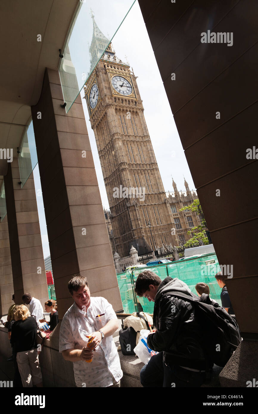 Tourists taking a snack break bu Big Ben on the Houses of Parliament - Stock Image