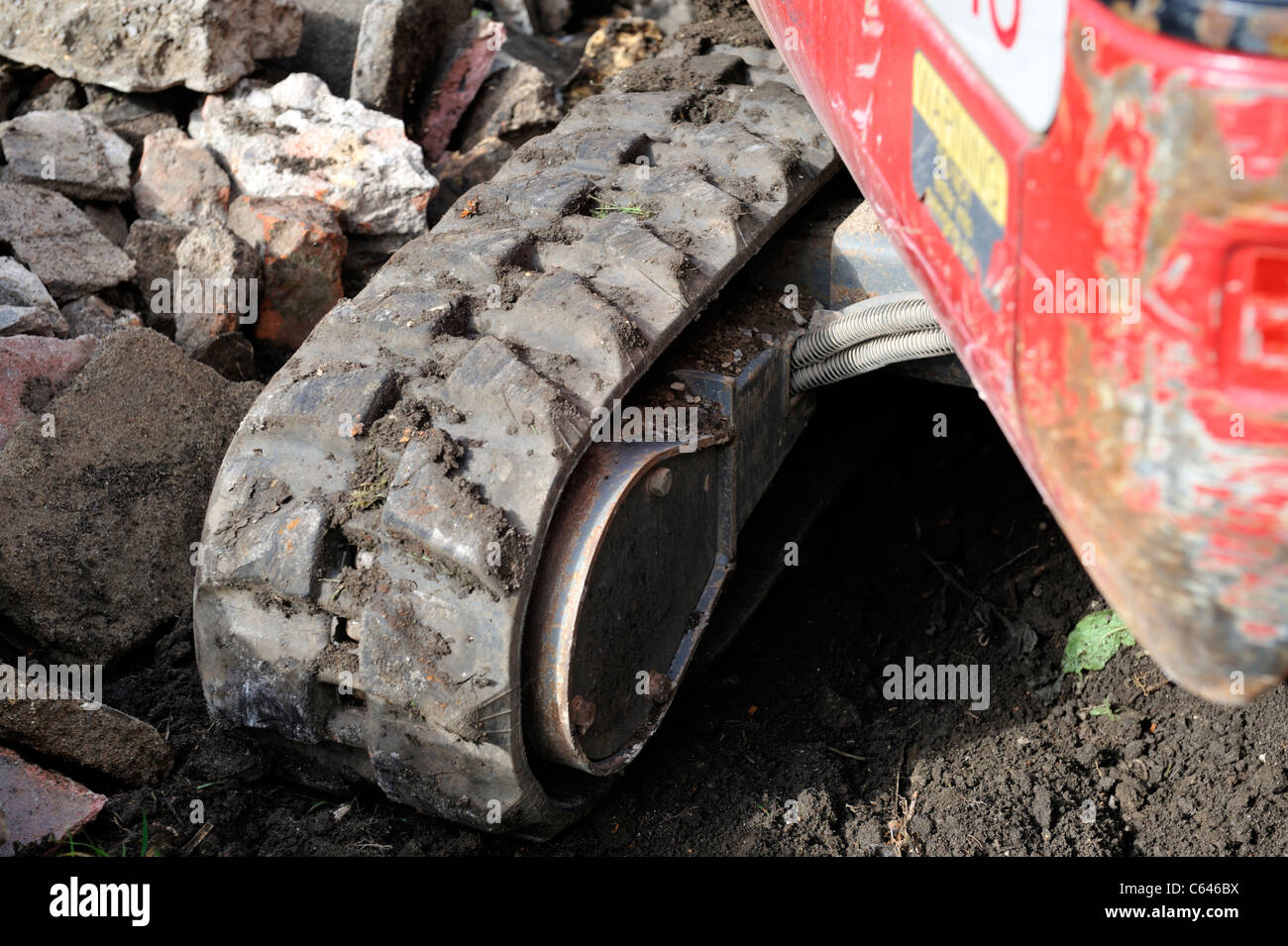 Detail of rubber padded continuous or caterpillar track on small digger machine - Stock Image