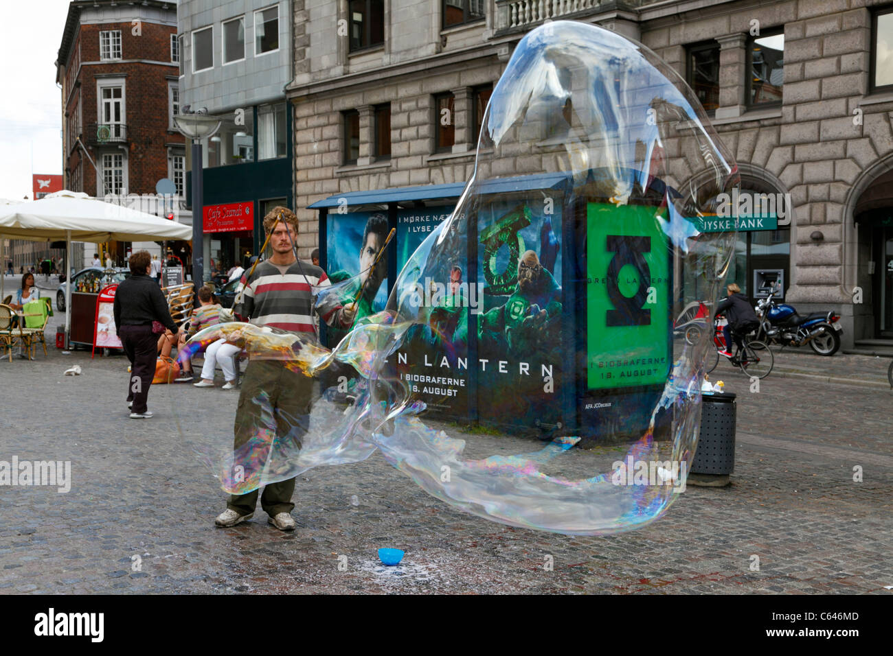 Young soap bubble street artist blowing giant soap bubbles on the pedestrian and shopping street Strøget in - Stock Image