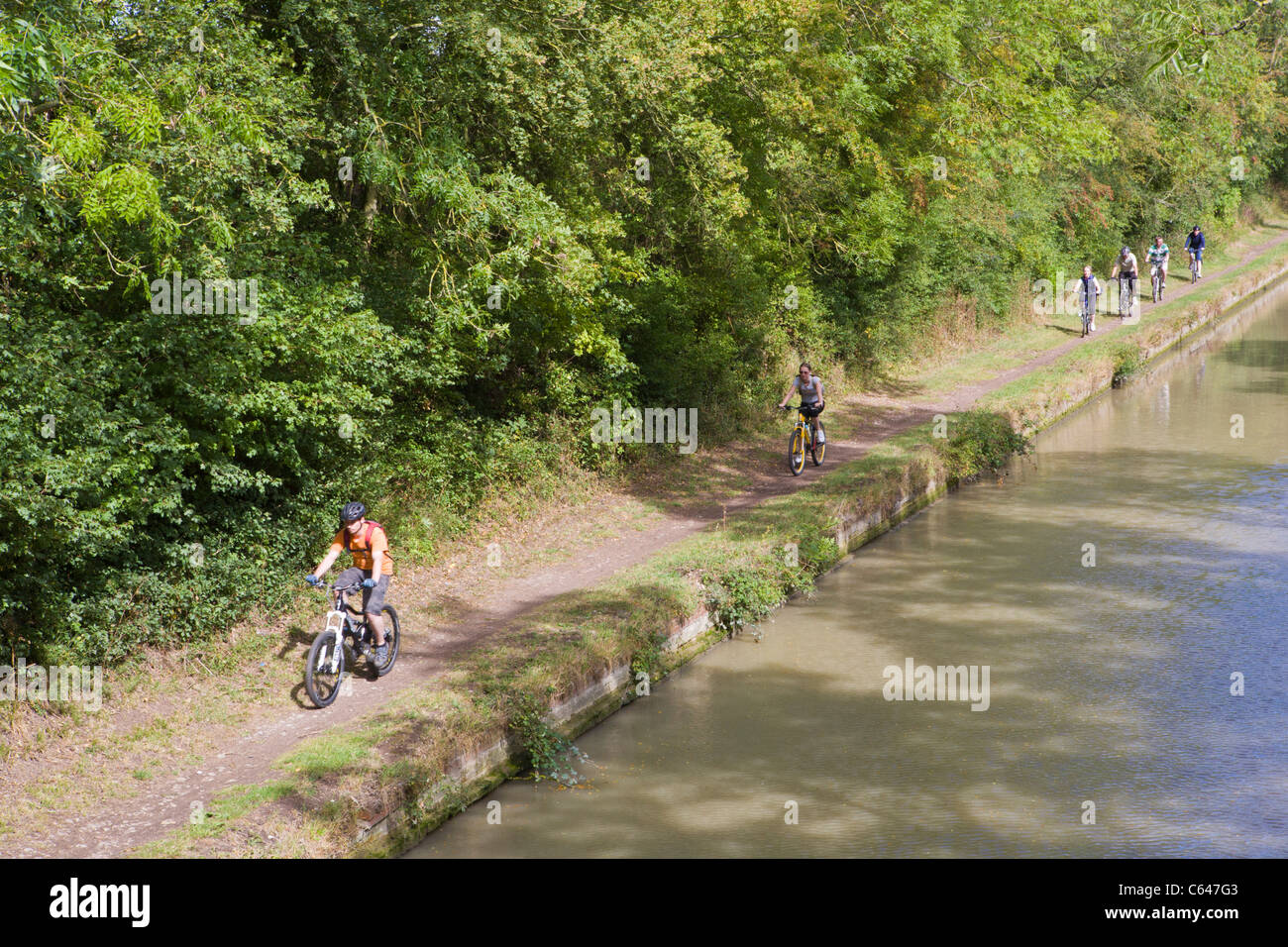 Cyclists riding along the towpath of the Grand Union Canal, Warwickshire, England. - Stock Image