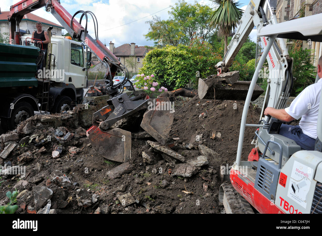 Mechanical excavators clearing ground residential garden Stock Photo