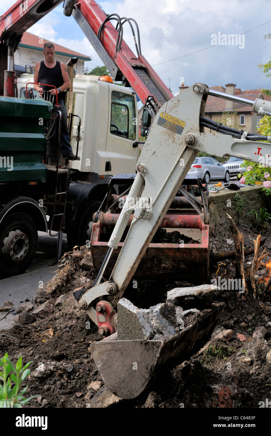 Mini digger and bucket scoop crane doing ground clearance of residential garden. Preparation for paving. Stock Photo