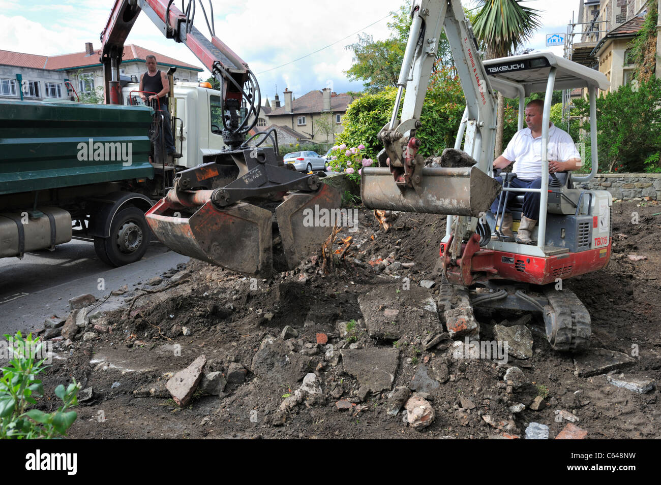 Mechanical excavators ground clearance of residential garden - Stock Image