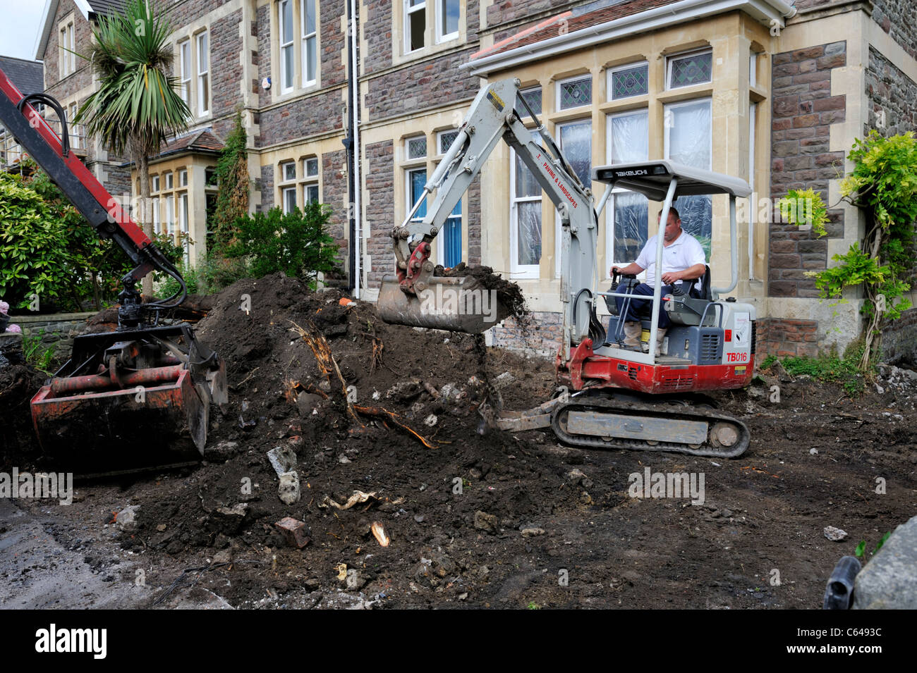 Mechanical mini digger and bucket scoop clearing ground of residential garden Stock Photo