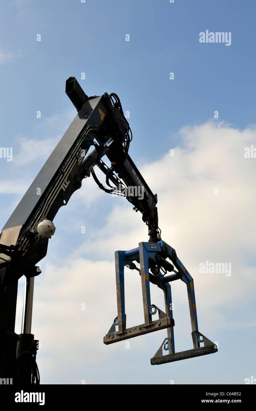 Crane with brick-grab for lifting pallets of bricks or blocks - Stock Image