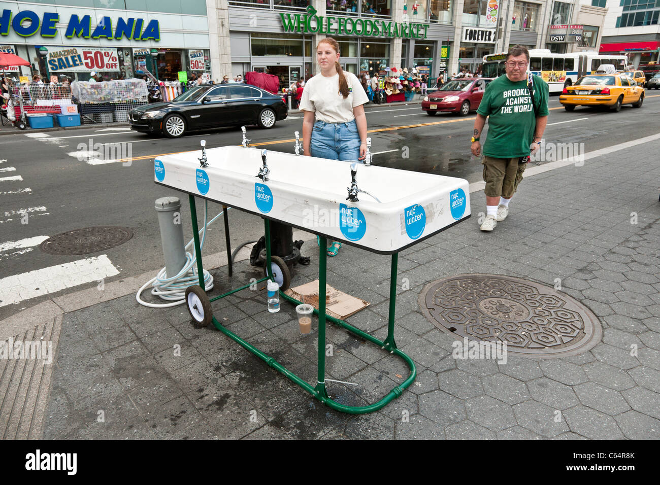 free temporary NYC tapwater drinking fountain manned by pretty volunteer on 14th Street at Union Square Manhattan - Stock Image