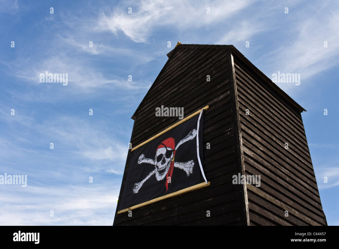 A skull and crossbones pirate flag on the side of a Net Shop in Hastings, Sussex. - Stock Image