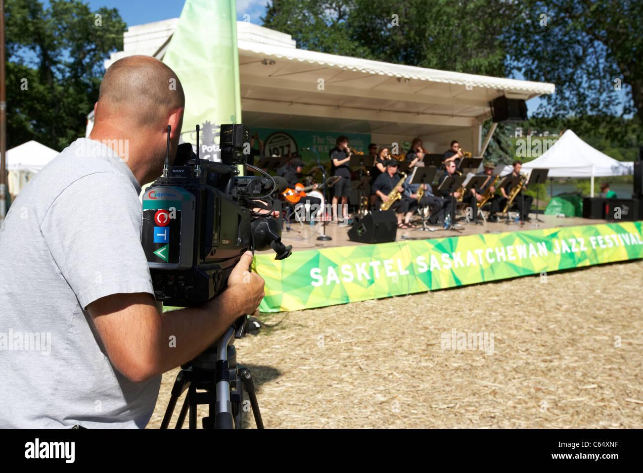 local ctv tv cameraman filming a band on stage at the sasktel Saskatoon jazz festival Saskatchewan Canada - Stock Image
