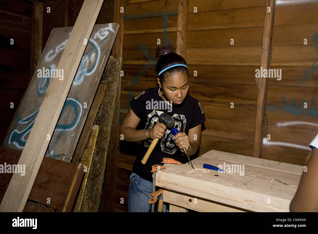 High school teen carves a sign in the Brightening Brightmoor summer project building a park in inner city Detroit - Stock Image