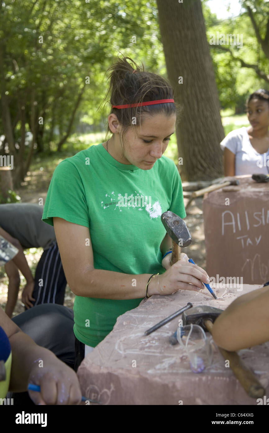 College student works on stone carving for a park being built by neighborhood youth and volunteers in inner city - Stock Image
