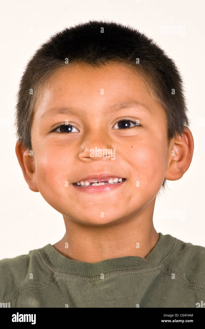Cute young 6-7 year old Hispanic boy with two front teeth missing multi inter racial diversity racially diverse - Stock Image