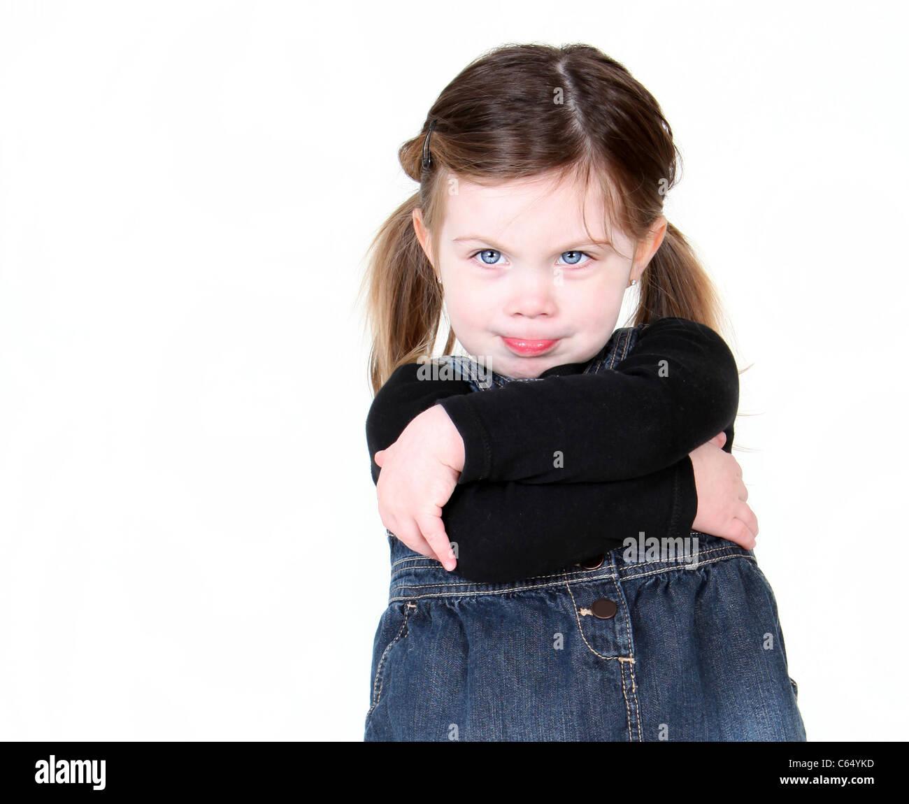 sassy child with arms folded on white with copyspace. - Stock Image