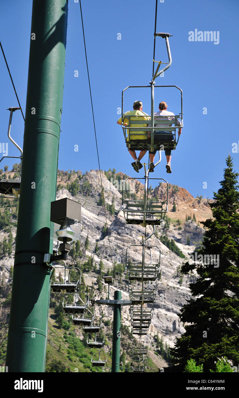 A couple ride the Chickadee ski lift at Snowbird Ski and Summer resort - Stock Image