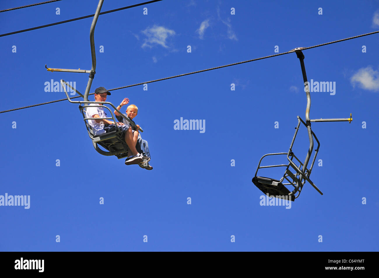 A father and son ride the Chickadee ski lift at Snowbird Ski and Summer resort - Stock Image