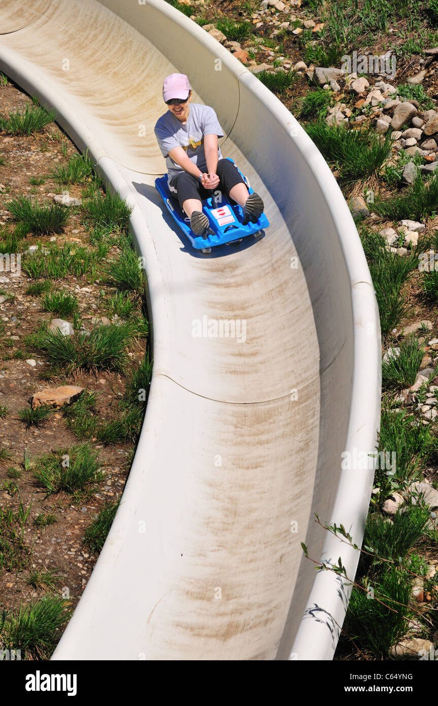 A young man zooms down the Alpine slide at Snowbird Ski and Summer Resort - Stock Image