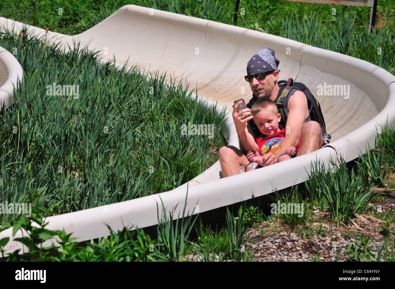 A father checks his cell phone while cradling his son on the Alpine Slide at Snowbird Ski and Summer Resort - Stock Image