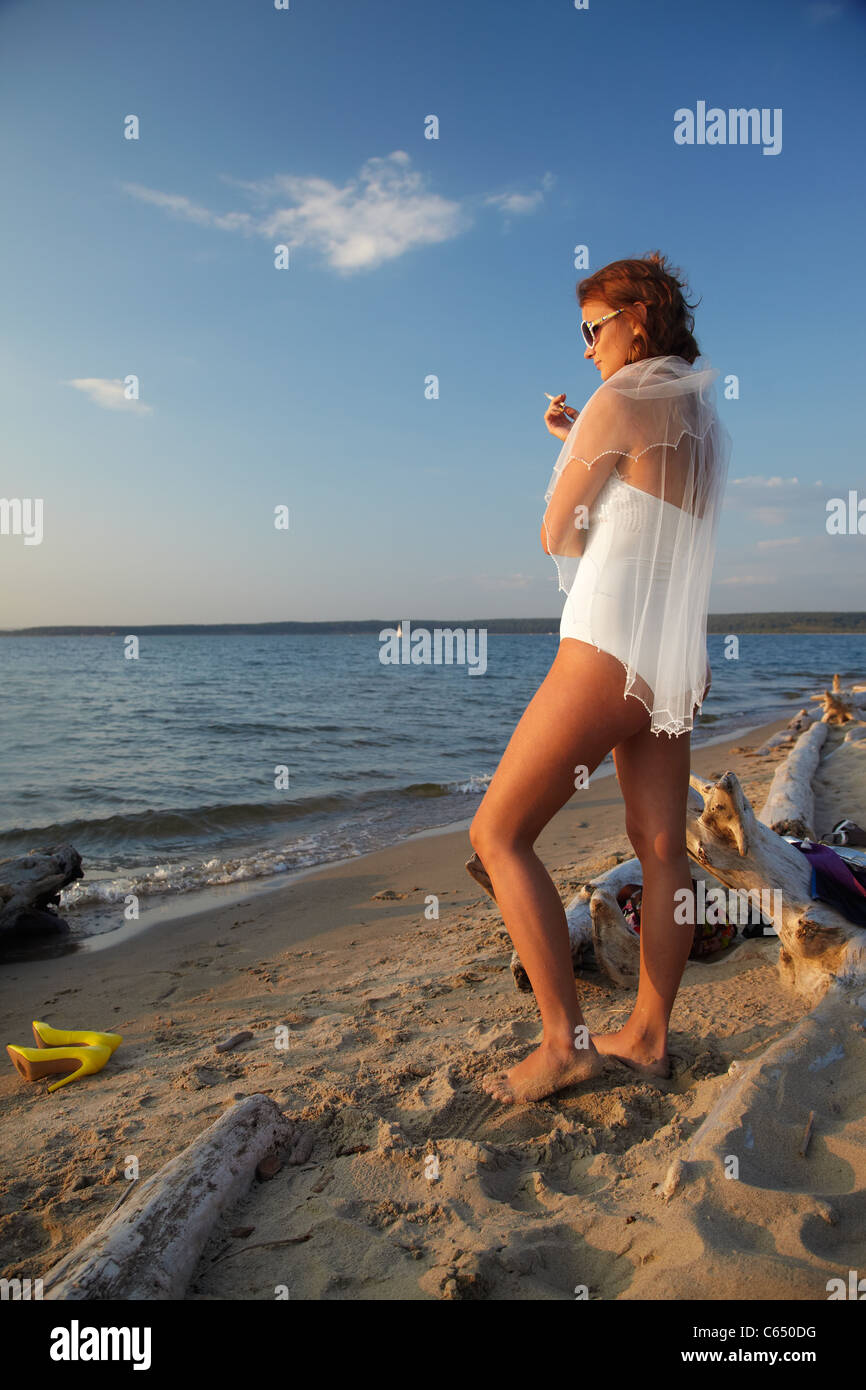 slavonic bride in body and sunglasses smokin on seashore - Stock Image