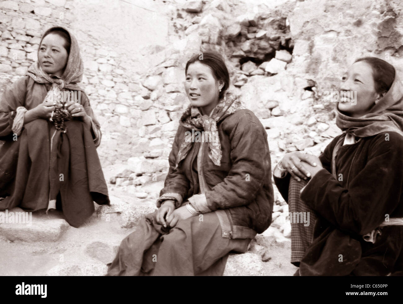 Tibetan Woman are sitting and talking outside their monastery in Tibet, Ladak, North India - Stock Image