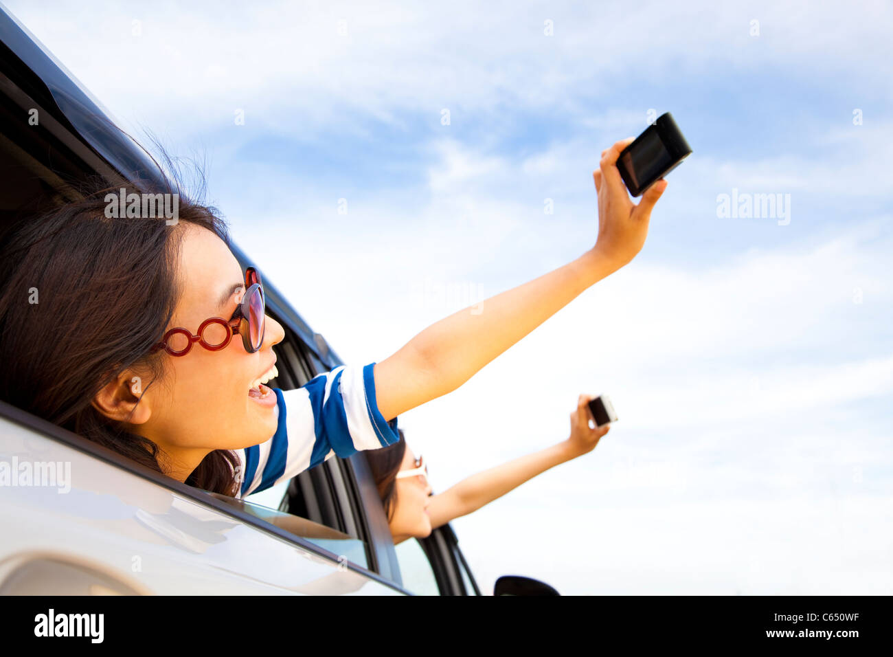 happy young woman holding camera and mobile phone taking photos in the car - Stock Image