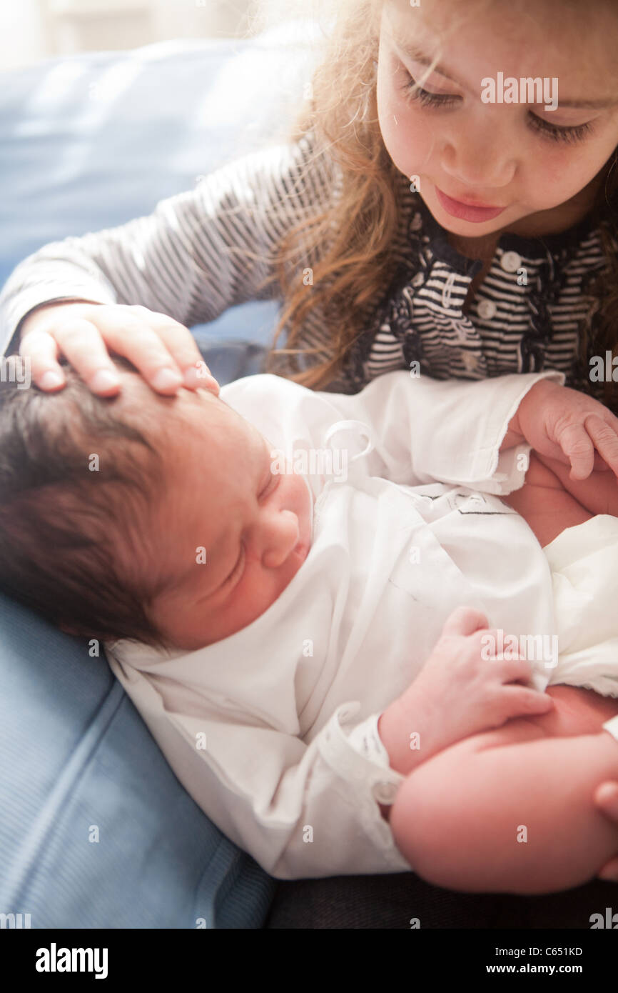 A Young Girl Caressing His Newborn Brother For The First Time In The Hospital Stock