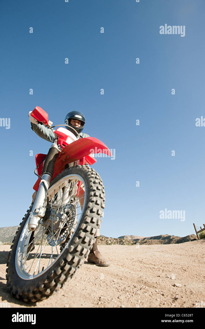 Man riding dirt bike on dirt track - Stock Image