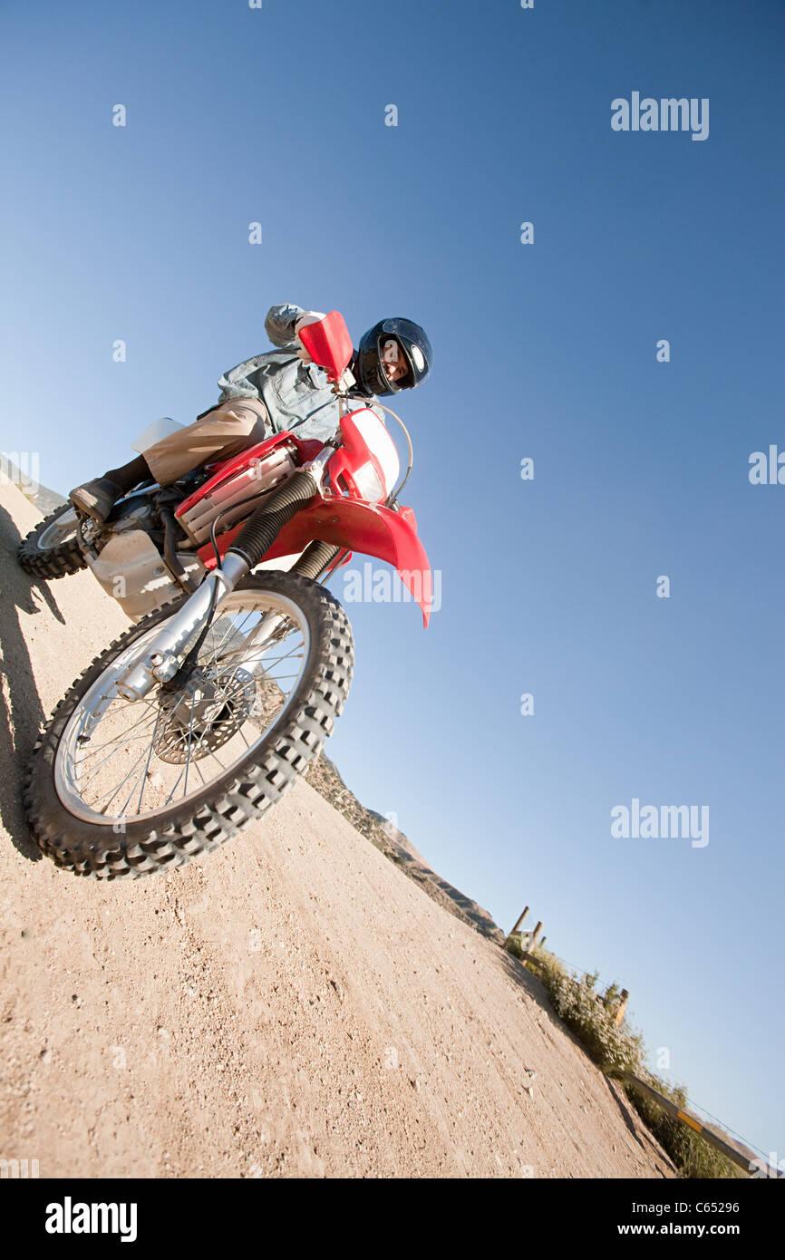 Man riding dirt bike on dirt track - Stock Image