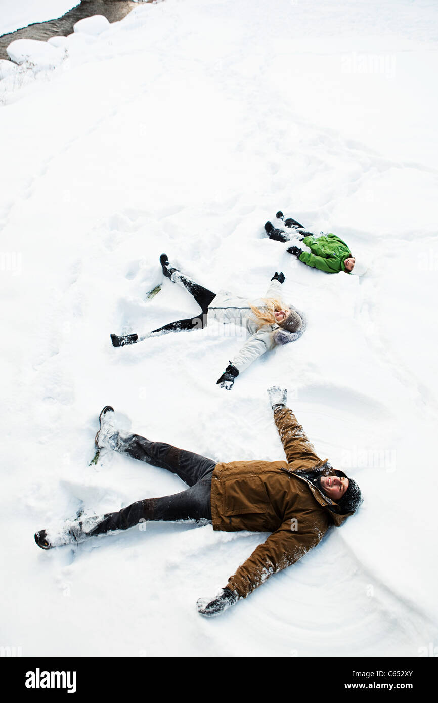 Family making snow angels - Stock Image