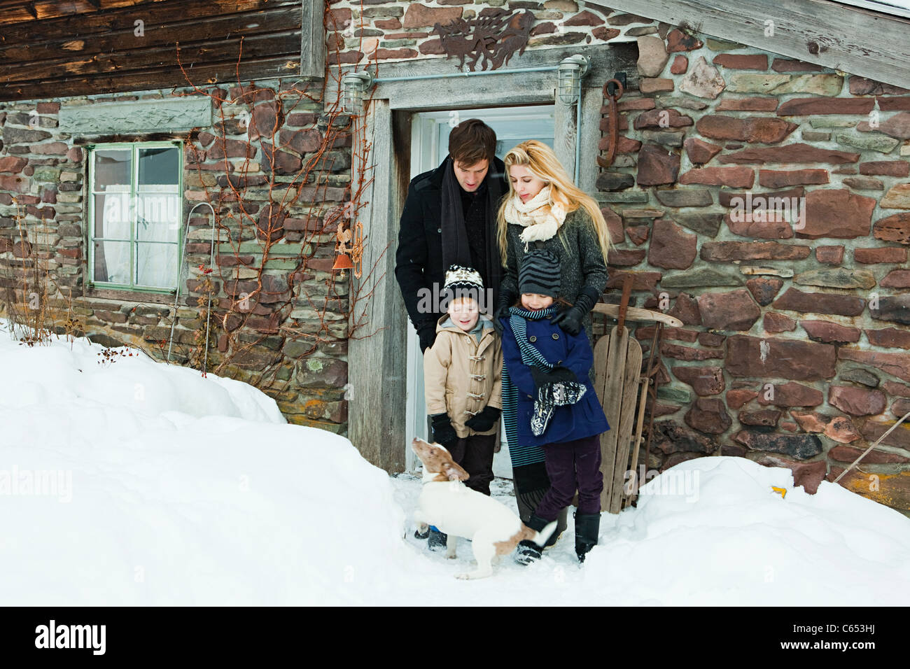 Family outside rustic house in snow - Stock Image