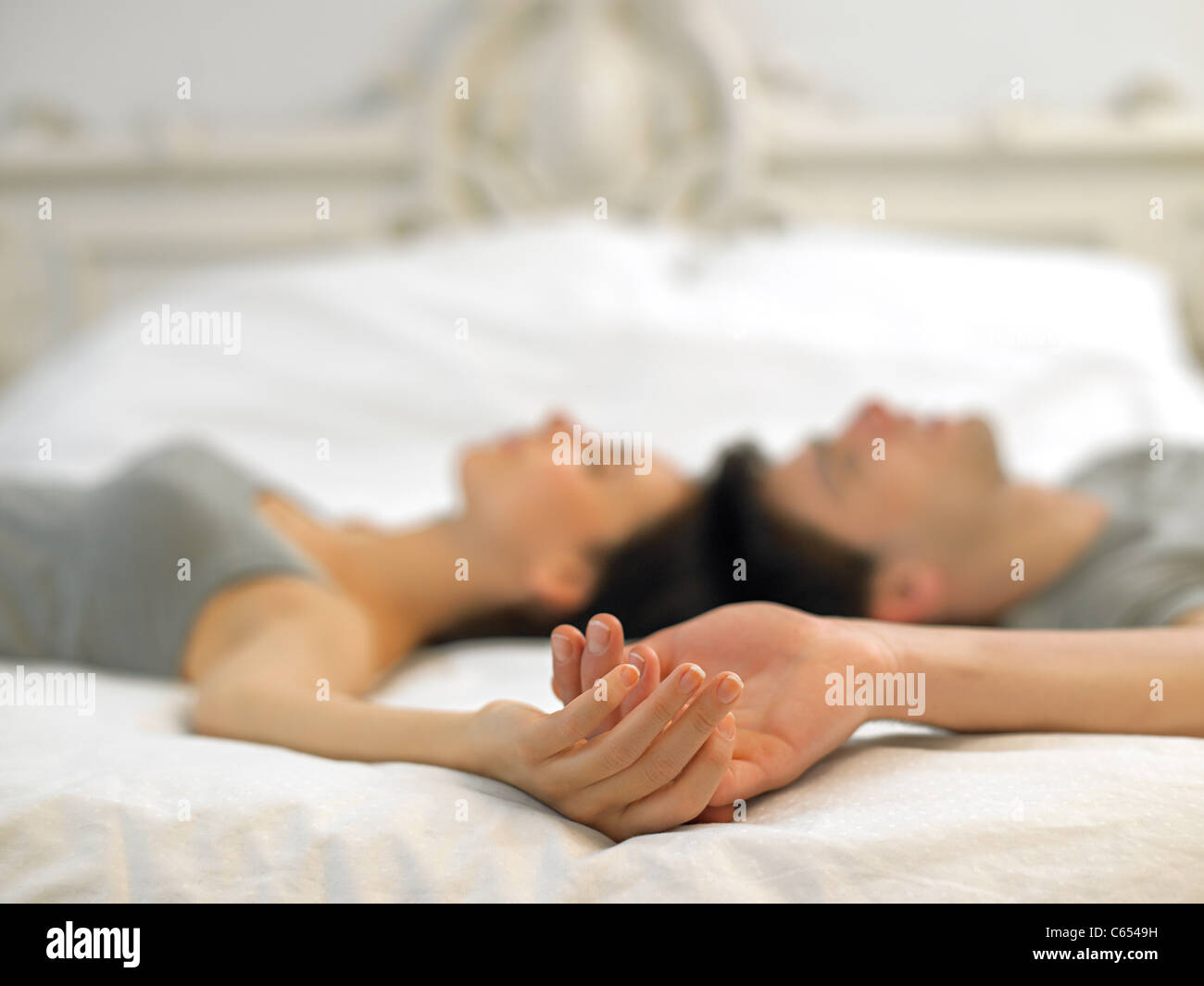 Young couple lying on bed holding hands - Stock Image