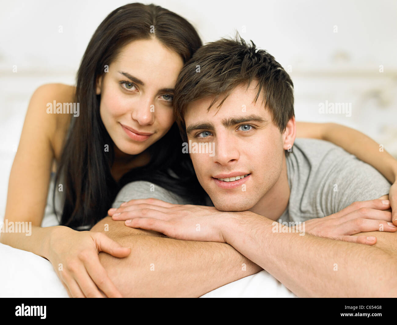 Young couple lying on front, portrait - Stock Image