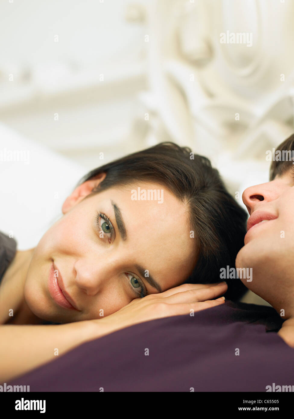 Young couple lying in bed, woman's head on man's shoulder - Stock Image