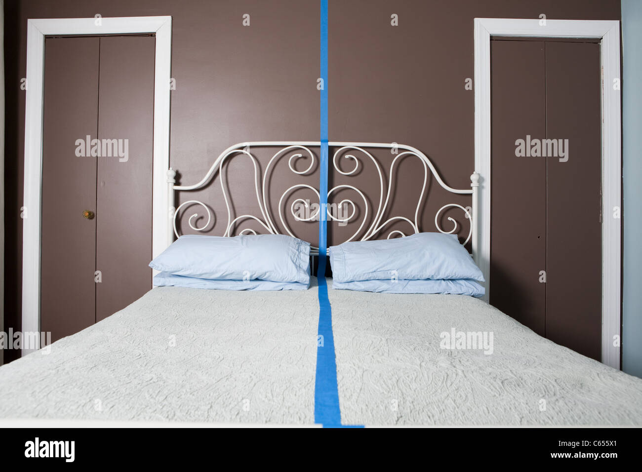 Double bed separated by blue line - Stock Image