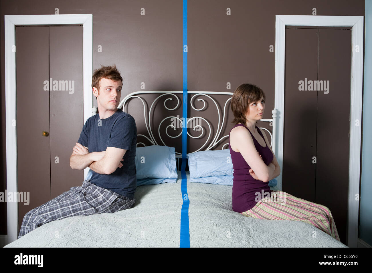 Young couple sitting on bed separated by blue line - Stock Image